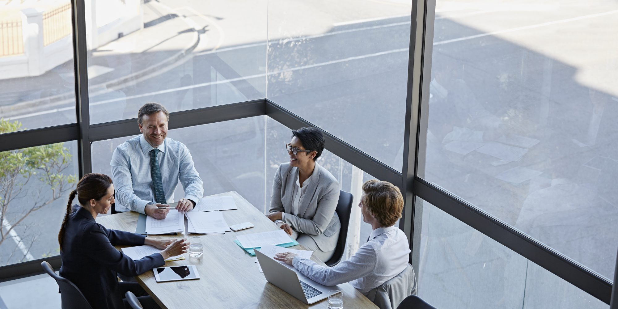 High angle view of smiling business people in meeting. Male and female professionals are sitting at conference table against window. They are working in office.